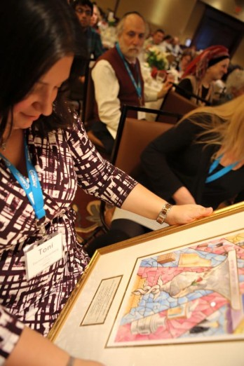 Toni admires Camp Interlaken's award that doubles as a beautiful piece of Jewish art.